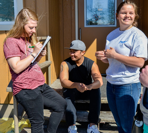 Prince William Sound College students hanging out on the steps of student housing in Valdez, Alaska.