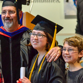 Prince William Sound College dual-credit student Emily Humphrey stands with her family during graduation