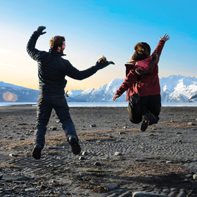 College students jumping for joy on a beach in Valdez, Alaska