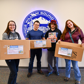 PWSC students hold up boxes used to collect food drive donations.