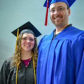 Larissa Williams, PWSC Graduate, stands in a graduation cap and gown with her husband.