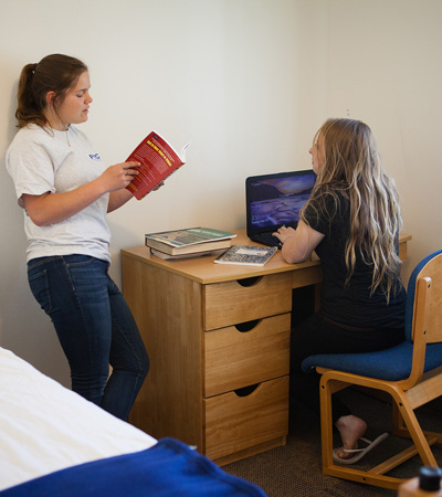 Students talking at a desk in Student Housing at Prince William Sound College in Valdez, Alaska.